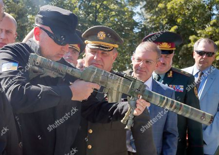 Secretary of Ukraine's National Security and Defence Council Oleksandr Turchynov, left, and Defence Minister, Stepan Poltorak, 2nd left, examine a Ukrainian-made new sample of a machine gun at a presentation of new weapons, on a tank plant in Kiev, Ukraine