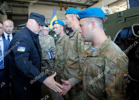 Oleksandr Turchynov Secretary of Ukraine's National Security and Defence Council Oleksandr Turchynov, left, shakes hand with servicemen at a presentation of new weapons, on a tank plant in Kiev, Ukraine