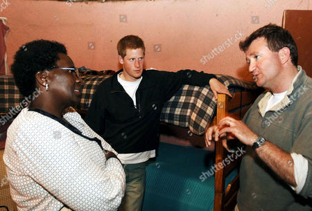 Stock Image of Prince Harry (centre) and Lydia Muso of the Lesotho children's counselling unit near to the capital of Maseru, listen to Geoffrey Matthews, of Sentebale, while on a return visit to Lesotho. The Prince was in the country to launch his new charity called 'Sentebale', which means 'Forget me not', to benefit children orphaned by AIDS