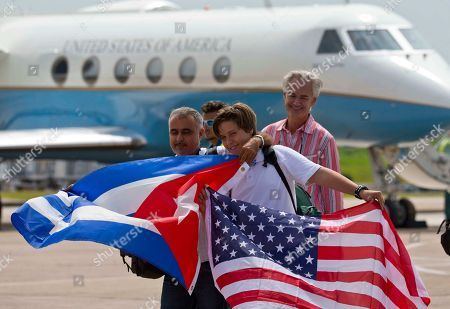 Passengers of JetBlue flight 387 holding a United States, and Cuban national flags, pose for photos in front of the plane transporting U.S. Transportation Secretary Anthony Foxx, at the airport in Santa Clara, Cuba, . JetBlue 387, the first commercial flight between the U.S. and Cuba in more than a half century, landed in the central city of Santa Clara on Wednesday morning, re-establishing regular air service severed at the height of the Cold War
