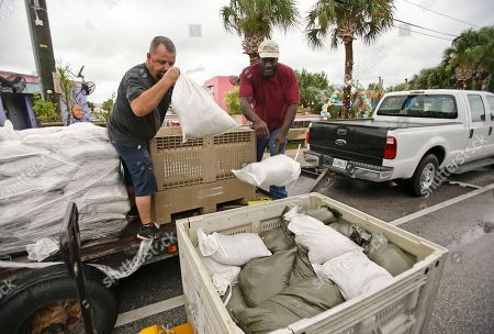Stock Image of Jerry Boyd, left, and Tommy Neal unload sandbags that will be used to shore up doorways at a restaurant as they prepare for Tropical Storm Hermine, in Cedar Key, Fla. Forecasters say Hermine could be near hurricane strength by Thursday night as it approaches the Gulf Coast