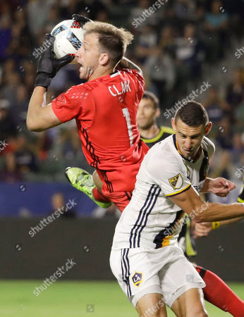 Columbus Crew goalkeeper Steve Clark, left, blocks a shot next to Los Angeles Galaxy defender Daniel Steres during the second half of an MLS soccer match, in Carson, Calif