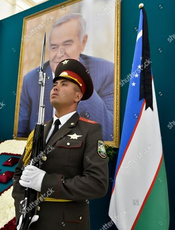 An Uzbek honor guard stands by a portrait of Uzbekistan's President Islam Karimov during a funeral ceremony in Samarkand, Uzbekistan, . Karimov, who crushed all opposition in the Central Asian country of Uzbekistan as its only president in a quarter-century of independence from the Soviet Union, has died of a stroke at age 78, the Uzbek government announced Friday