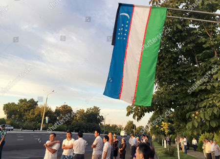 People gather along the road under the Uzbekistan national flag with a black ribbon to watch the funeral procession of President Islam Karimov in Tashkent, Uzbekistan, early . Karimov has died of a stroke at age 78, the Uzbek government announced Friday