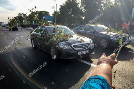 People throw flowers on limousines as they gather along a road to watch the funeral procession of President Islam Karimov in Tashkent, Uzbekistan, early . Karimov has died of a stroke at age 78, the Uzbek government announced Friday