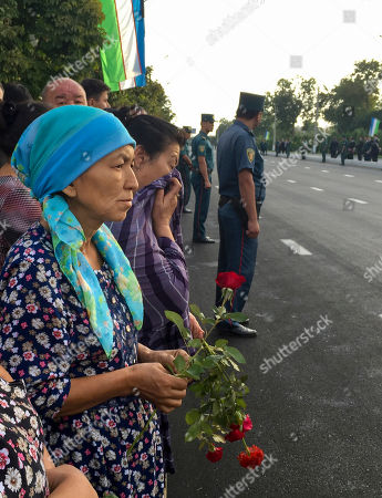 People gather along the road under the Uzbekistan national flag to watch the funeral procession of President Islam Karimov in Tashkent, Uzbekistan, early . Karimov has died of a stroke at age 78, the Uzbek government announced Friday