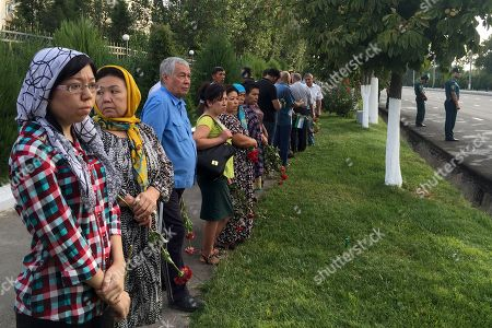 People with flowers gather along the road to watch the funeral procession of President Islam Karimov in Tashkent, Uzbekistan, early . Karimov has died of a stroke at age 78, the Uzbek government announced Friday