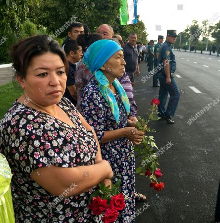 People hold flowers as they gather along the road under the Uzbekistan national flag to watch the funeral procession of President Islam Karimov in Tashkent, Uzbekistan, early . Karimov has died of a stroke at age 78, the Uzbek government announced Friday