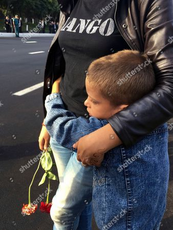 A woman embraces her son while standing along the road to watch the funeral procession of President Islam Karimov in Tashkent, Uzbekistan, early . Karimov has died of a stroke at age 78, the Uzbek government announced Friday