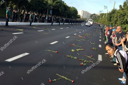 Police guard as people gather along a road to watch the funeral procession of President Islam Karimov in Tashkent, Uzbekistan, early . Karimov has died of a stroke at age 78, the Uzbek government announced Friday