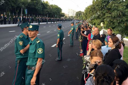 Police secure an area as people with flowers gather along the road to watch the funeral procession of President Islam Karimov in Tashkent, Uzbekistan, early . Karimov, who crushed all opposition in the Central Asian country of Uzbekistan as its only president in a quarter-century of independence from the Soviet Union, has died of a stroke at age 78, the Uzbek government announced Friday