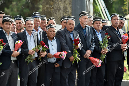 People hold flowers as they gather along the road to watch the funeral procession of President Islam Karimov in Samarkand, Uzbekistan, . Karimov has died of a stroke at age 78, the Uzbek government announced Friday. Karimov will be buried Saturday in the ancient city of Samarkand, his birthplace, the government said in a statement