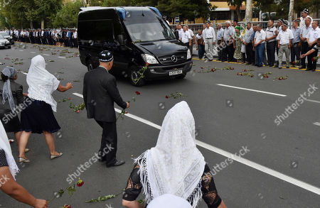 People throw flowers on the hearse as they gather along the road to watch the funeral procession of President Islam Karimov in Samarkand, Uzbekistan, early . Karimov has died of a stroke at age 78, the Uzbek government announced Friday. Karimov will be buried Saturday in the ancient city of Samarkand, his birthplace, the government said in a statement