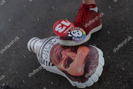 """A man steps on a inflatable doll with the image of Senator Aecio Neves with two stickers on his shoe that read in Portuguese """"Temer out"""" and """"Dilma 13,"""" at a camp in support of Brazil's suspended President Dilma Rousseff, in Brasilia, Brazil, . Rousseff will face Congress on Monday as her impeachment process enters its final stages. She is accused of using unauthorized loans from state-owned banks and that she illegally issued decrees to make government payments without congressional approval"""