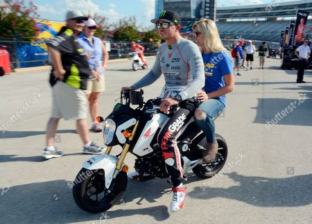 Stock Image of Graham Rahal, Courtney Rahal Graham Rahal and his wife, Courtney Force, ride a scooter away pit road after a warm-up period for the resumption of an IndyCar auto race stopped in June, at Texas Motor Speedway, in Fort Worth, Texas
