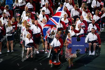 Great Britain are led out by flagbearer Lee Pearson.