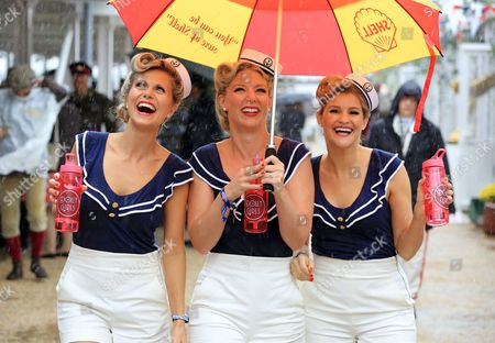 Stock Image of The Dolly Girls: Hannah Woolley, Helen Patching, Katy Osborne, dressed in vintage sailor outfits during the wet weather