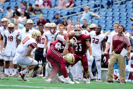 Massachusetts Minutemen quarterback Ross Comis (2) fumbles the ball while being tackled by Boston College Eagles defensive back Isaac Yiadom (20)
