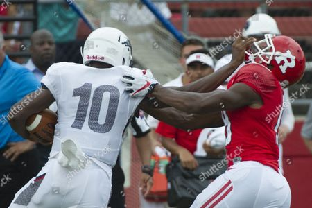 Howard Bison quarterback Jason Collins (10) stiff arms Rutgers Scarlet Knights defensive back Damon Hayes (18)