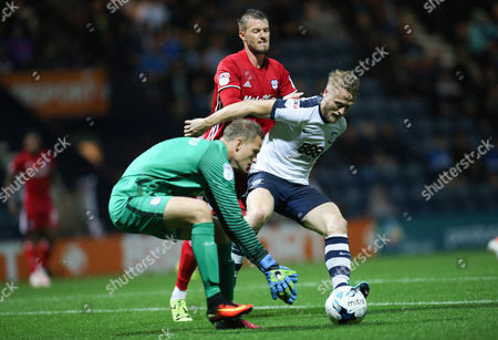 Tom Clarke of Preston North End holds off Anthony Pilkington of Cardiff City as Preston North End?s goalkeeper Anders Lindegaard collects the ball