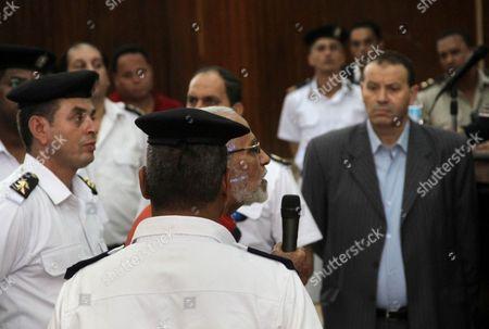 Stock Photo of Egyptian Muslim Brotherhood leader Mohammed Badie speaks to judges during his trial