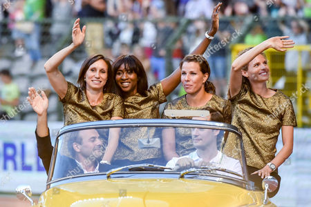 Belgium athletes, Kim Gevaert, Elodie Ouedraogo, Hanna Mariën and Olivia Borlee, from background left, greet the public as they sit in an open car at a Diamond League Memorial Van Damme athletics event, at the King Baudouin stadium in Brussels on . The Belgian 2008 women's Olympic 4x100 relay team was officially handed its gold medals on Friday ? eight years after crossing the line at the Beijing Games in second place behind Russia. The team moved up to gold this year after a Russian runner was caught doping in a retest