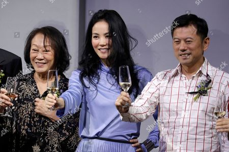 """Chinese pop singer Faye Wong, center, toasts champagne on stage to launch her """"Faye's Moment"""" concert, in Beijing, . Wong will hold her concert at the Mercedes-Benz Arena in Shanghai, China on Dec. 30, 2016"""