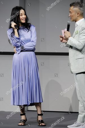 """Chinese pop singer Faye Wong, left, speaks to a host during a press conference in Beijing, . Wong is in Beijing to launch her """"Faye's Moment"""" concert which will held at the Mercedes-Benz Arena in Shanghai, China on Dec. 30, 2016"""