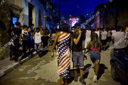 Stock Photo of A woman wearing a dress with a U.S. flag motif walks to a concert by Silvio Rodriguez in Guanabacoa on the outskirts of Havana, Cuba, . President Barack Obama's easing of the U.S. trade embargo on Cuba has had virtually no positive effect on the island's economy, Cuba's top diplomat asserted Friday