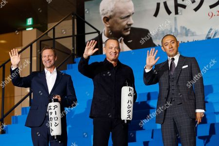 """Stock Image of Tom Hanks, Aaron Eckhart, Ebizo Ichikawa Tom Hanks, center, Aaron Eckhart, left, holding lanterns written with their names in Japanese letters and Japanese traditional kabuki actor Ebizo Ichikawa wave for fans during the Japan premiere of """"Sully"""" in Tokyo"""