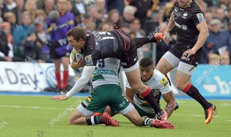 Saracens' Alex Goode is lifted in a tackle by Northampton's Lee Dickson