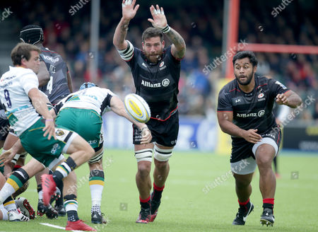 Jim Hamilton and Billy Vunipola of Saracens look to block a kick by Lee Dickson of Northmpton