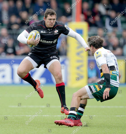 Alex Goode of Saracens runs at Lee Dickson of Northampton