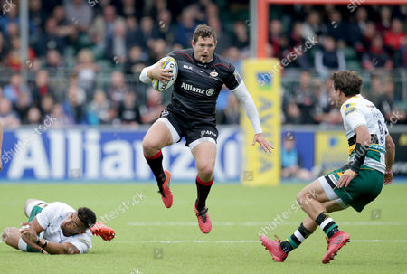 Alex Goode of Saracens gets away from Luther Burrell of Northampton (on ground) and takes on Lee Dickson