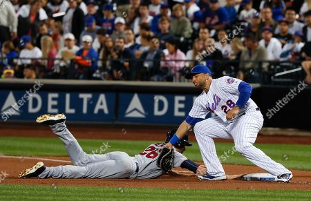 New York Mets first baseman James Loney (28) tags out Minnesota Twins' Max Kepler (26) on a pick-off at first base during the fourth inning of a baseball game, in New York. Kepler was initially called safe by the umpire, but the call was overturned on a challenge by Mets manager Terry Collins