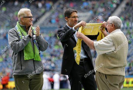 Gary Wright, Adrian Hanauer, Drew Carey Gary Wright, right, Former Sounders senior vice president of business operations, is presented with the Golden Scarf award by Sounders owners Adrian Hanauer, center, and Drew Carey, left, before an MLS soccer match, in Seattle. Wright was honored for his role in the Sounders organization including the beginning of MLS play in 2009