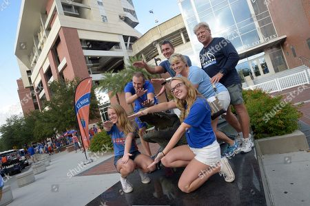Florida fans pose on the Bull Gator statue outside Ben Hill Griffin Stadium before an NCAA college football game against North Texas in Gainesville, Fla