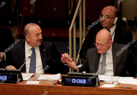 Mevlut Cavusoglu, Foreign Minister for Turkey, left, and Tammam Salam, right, Prime Minister of Lebanon, take each other's hands while leading a meeting addressing actions and cooperation on the large movement of refugees and migrants, at U.N. headquarters