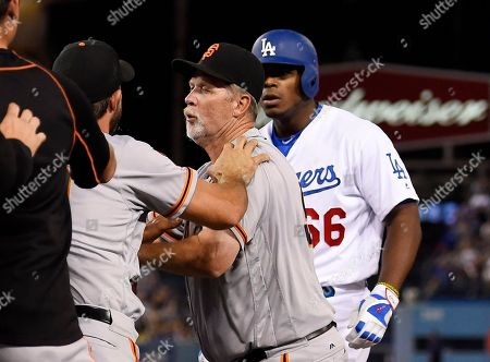 Madison Bumgarner, Yasiel Puig, Bill Hayes San Francisco Giants starting pitcher Madison Bumgarner, second from left, and Los Angeles Dodgers' Yasiel Puig, right, argue as first base coach Bill Hayes stands between them during a scuffle that emptied both benches after Puig was thrown out at first by Bumgarner during the seventh inning of a baseball game, in Los Angeles