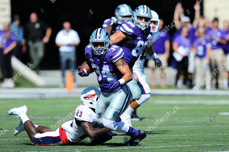 Stock Image of Kansas State Wildcats running back Alex Barnes (34) tries to break a shoestring tackle by Florida Atlantic Owls defensive back Raekwon Williams (23)
