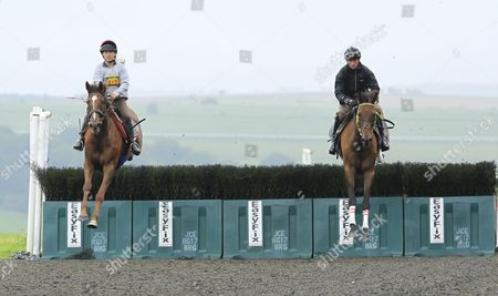 Stock Picture of Coneygree and Nico De Boinville [right] schooling over fences in Lambourn with Step Back ridden by Lily Bradstock daughter of trainer Mark.