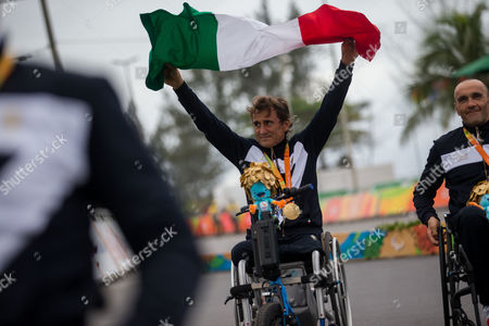 Alessandro Zanardi holds an Italian flag as he celebrates with teammates after Italy won the gold medal of the men's team relay H2-5 road cycling final at the Rio 2016 Paralympic games at Pontal beach in Rio de Janeiro, Brazil, . Italy's team Vittorio Pedestal, Luca Mazzone and Zanardi won the gold medal, the US got silver and Belgium bronze