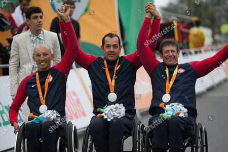 From left to right, William Groulx, Oscar Sanchez and William Lachenauer, from the United States celebrate the silver medal after the men's team relay H2-5 road cycling final at the Rio 2016 Paralympic games at Pontal beach in Rio de Janeiro, Brazil, . Italy's team Vittorio Pedestal, Luca Mazzone and Alessandro Zanardi won the gold medal, the US got silver and Belgium bronze