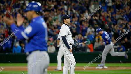 Hisashi Iwakuma Seattle Mariners starting pitcher Hisashi Iwakuma, center, stands on the mound as Toronto Blue Jays' Michael Saunders, right, rounds the bases after he hit a two-run home run in the fourth inning of a baseball game, in Seattle
