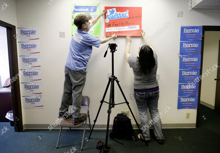 Matt Keating, left, and Jessica Smith hang signs on a wall as they await the arrival of Democratic presidential candidate Sen. Bernie Sanders at an open house at his Iowa campaign headquarters, in Des Moines, Iowa