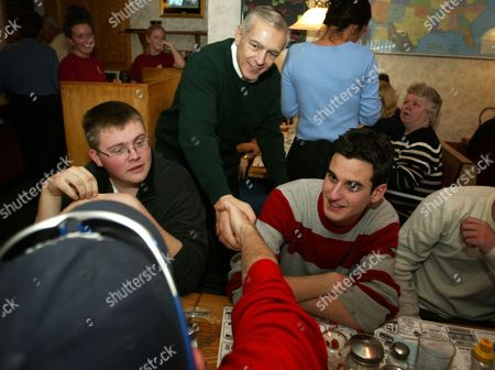 CLARK BURNS FLAHIVE Democratic presidential hopeful Wesley Clark, center, makes a campaign stop at Belmont Restaurant as students Charles Burns, left, and Tom Flahive, look on in Manchester, N.H