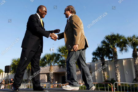 Herman Cain greets Michael Reagan, son of former President Ronald Reagan, as they campaign for Republican presidential candidate former House Speaker Newt Gingrich during a campaign stop, in Fort Myers, Fla