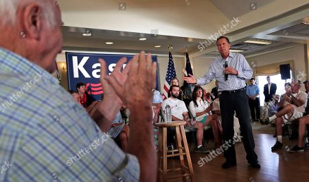 John Kasich An audience guest applauds as Republican presidential candidate Ohio Gov. John Kasich addresses a gathering during a town hall style meeting in Greenland, N.H