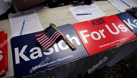 John Kasich Campaign signs, American flags and volunteer sign-up sheets rest on a table prior to a town hall style meeting by Republican presidential candidate Ohio Gov. John Kasich in Greenland, N.H