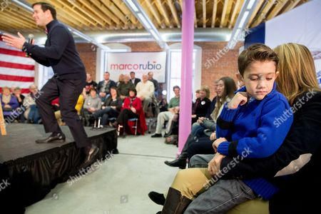 Marco Rubio, Jeanette Dousdebes, Dominic Rubio Republican presidential candidate, Sen. Marco Rubio, R-Fla., takes the stage as Dominic Rubio, 8, sits in the lap of Jeanette Dousdebes, Rubio's wife as he speaks at the Maytag Innovation Center in Newton, Iowa